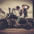 Biker and his bobber style motorcycle on a city streets — Stock Photo #70888893