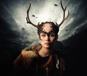 Woman shaman in ritual garment over dramatic stormy sky — Stock Photo