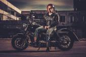 Biker and his bobber style motorcycle on a city streets  — Stock Photo