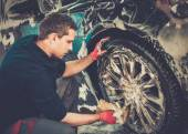 Man worker washing car's alloy wheels on a car wash  — Stock Photo