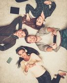 Happy multiracial friends relaxing on a carpet with gadgets  — Stock fotografie