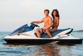 Multinational couple sitting on a jet ski — Stock fotografie