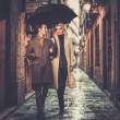 Elegant couple with umbrella walking outdoors in the rain — Stock Photo #71494283