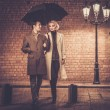 Elegant couple with umbrella walking outdoors in the rain — Stock Photo #71494319