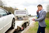 Man calling while tow truck picking up his broken car — Stock Photo