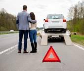 Couple near tow-truck picking up broken car — Stock Photo