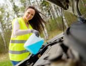Woman adding washing fluid on a roadside — Stock Photo