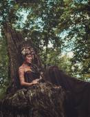 Nymph sitting on her throne in a magical forest — Stock Photo