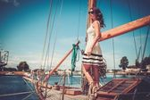 Stylish wealthy woman on wooden regatta — Stock Photo