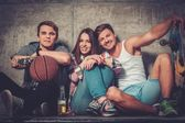 Cheerful friends with with skateboard and ball — Stock Photo