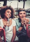 Multiracial couple having snack while riding on a sightseeing bus — Stock Photo