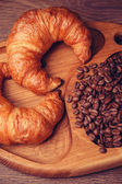 Croissants and coffee beans on a wooden board — Stock Photo