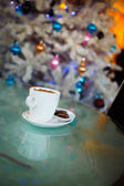 White cup of coffee under the christmas tree — Stock Photo