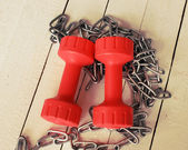Red dumbbells and metal chain — Stock Photo
