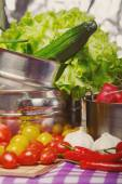 Different vegetables and pots on colored tablecloth — Stock Photo