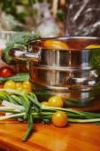 Steinless steel stockpot and vegetables around it — Stock Photo