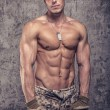 Strong athletic man with naked body in military pants — Stock Photo #61687015