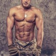 Strong athletic man with naked body in military pants — Stock Photo #61687031