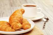 Plate with croissants and a cup of coffee — Stock Photo