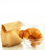Two croissants in a bowl and a paper bag — Stock Photo
