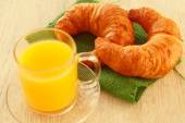 Two croissants on a green napkin and a mug of juice — Stock Photo