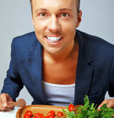 A man in a blue blazer happy to eat vegetables — Stock Photo