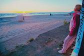 Beautiful girl watching sunset on urban beach — Stock Photo