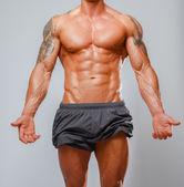 Muscular man bodybuilder poses — Stockfoto