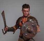 Gladiator holds sword and shield — Stock Photo