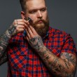 Brutal tattooed male shawing his beard — Stock Photo #63869701