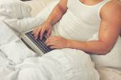 Man using laptop, sitting on bed — Stock Photo