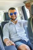 Happy male wit beart and tattoe in a car. — Stock Photo
