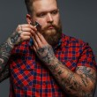 Brutal tattooed male shawing his beard — Stock Photo #65333335