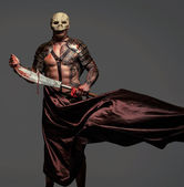 Tattooed medievel fighter in skull mask — Stock Photo