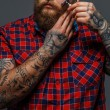 Brutal tattooed male shawing his beard — Stock Photo #68915931