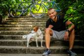 Man with dog sitting on stairs.  — Stock Photo