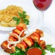 Table with food of meat on skewer, dumplings and gass of red win — Stock Photo #53532181
