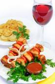 Table with food of meat on skewer, dumplings and gass of red win — Stock Photo