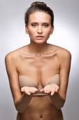 Beautiful woman in flesh color underwear showing by hand. — Stock Photo