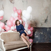 Young woman on the sofa  in a room full of inflatable balloons — Stok fotoğraf