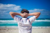 Handsome young man  against bright beach background, relaxes his hands behind  head — Stock Photo
