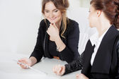 Girl showing something to her colleague, work in the office — Stock Photo