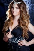 Beautiful girl  with long brown curled hair, dark background, vertical cropping — Stock Photo