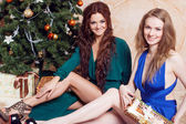 Two friends at the party, girl sitting under Christmas tree — Stock Photo
