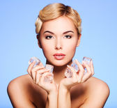 Beautiful young woman with ice in her hands. — Stock Photo