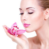 Beautiful woman with a pink orchid — Stock Photo