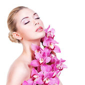 Beautiful woman with a pink orchids — Stock Photo