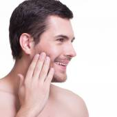 Smiling young man with hand near the face. — Stock Photo