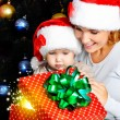 Mother with little child open gifts on christmas — Stock Photo #54824167