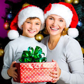 Mother with child hold box with gift on the christmas — Stockfoto